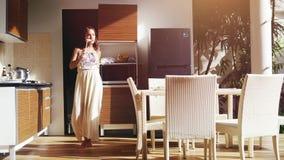 Gelukkige jonge vrouw die en in de keuken zingen dansen terwijl het maken van ontbijt in langzame motie 3840x2160 stock video