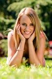 Gelukkige jonge vrouw die in garss en het glimlachen leggen Royalty-vrije Stock Afbeeldingen