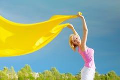 Gelukkige jonge vrouw die gele sjaal in de wind houdt Stock Foto's