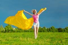 Gelukkige jonge vrouw die gele sjaal in de wind houdt stock afbeeldingen