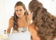 Gelukkige jonge vrouw die gezichtshuidvoorwaarde controleren Royalty-vrije Stock Foto