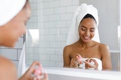 Gelukkige jonge vrouw die gezichtsroom in badkamers toepassen stock foto
