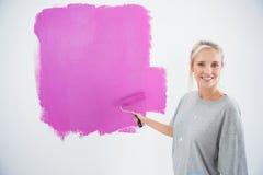 Gelukkige jonge vrouw die haar schilderen muurroze Royalty-vrije Stock Afbeeldingen
