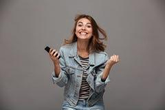 Gelukkige jonge vrouw die in jeansjasje haar vuisten in winnaar dichtklemmen royalty-vrije stock fotografie