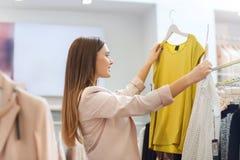 Gelukkige jonge vrouw die kleren in wandelgalerij kiezen Royalty-vrije Stock Fotografie