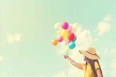 Gelukkige jonge vrouw die kleurrijke ballons met het drijven houden Royalty-vrije Stock Foto
