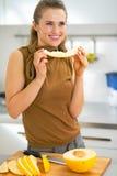 Gelukkige jonge vrouw die meloen in keuken eten Royalty-vrije Stock Afbeeldingen