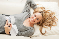 Gelukkige jonge vrouw die met boek ligt stock fotografie