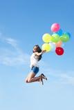 Gelukkige jonge vrouw die met kleurrijke ballons springen Stock Fotografie