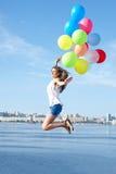 Gelukkige jonge vrouw die met kleurrijke ballons springen Stock Afbeelding