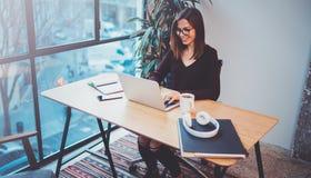 Gelukkige jonge vrouw die mobiele laptop voor het maken van bedrijfsgesprek met partners tijdens het werkproces op nachtkantoor m royalty-vrije stock fotografie