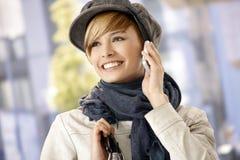 Gelukkige jonge vrouw die mobiele telefoon in openlucht met behulp van stock foto's