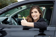 Gelukkige jonge vrouw die in nieuwe auto camera het glimlachen omhoog duim kijken Stock Fotografie