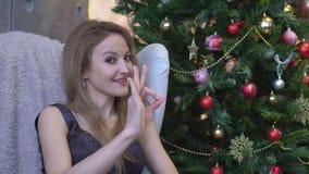Gelukkige jonge vrouw die o.k. teken met vingers knipogen tonen geïsoleerd op een achtergrond van de Kerstmisboom stock footage