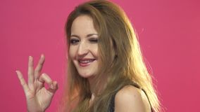 Gelukkige jonge vrouw die o.k. teken met vingers knipogen tonen geïsoleerd op een roze achtergrond stock videobeelden