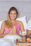 Gelukkige jonge vrouw die ontbijt in bed met partner hebben Stock Afbeeldingen