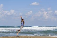 Gelukkige jonge vrouw die op het strand springt stock afbeeldingen