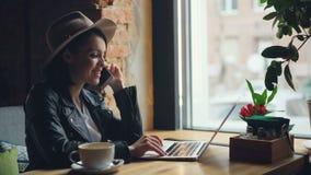 Gelukkige jonge vrouw die op mobiele telefoon spreken en laptop het typen in koffie gebruiken stock footage