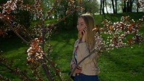 Gelukkige jonge vrouw die op slimme telefoon in park babbelen stock footage