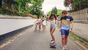 Gelukkige jonge vrouw die op vleet met haar vrienden berijden stock afbeeldingen