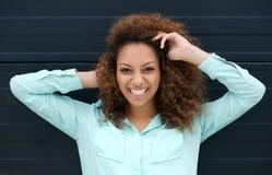 Gelukkige jonge vrouw die in openlucht tegen zwarte achtergrond glimlachen Royalty-vrije Stock Foto