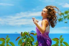 Gelukkige jonge vrouw die over blauwe hemel springt Stock Afbeeldingen