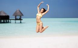 Gelukkige jonge vrouw die over exotisch strand springen Stock Afbeeldingen