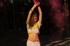 Gelukkige jonge vrouw die pret hebben bij Holi-festival in het park Royalty-vrije Stock Foto's