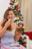 Gelukkige jonge vrouw die in pyjama's koekjes eten stock afbeeldingen