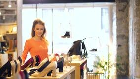 Gelukkige jonge vrouw die schoenen kiezen bij opslag stock video