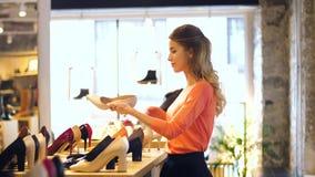 Gelukkige jonge vrouw die schoenen kiezen bij opslag stock footage
