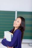 Gelukkige jonge vrouw die in school omhoog kijken stock fotografie