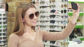 Gelukkige jonge vrouw die selfies terwijl het winkelen voor eyewear nemen stock videobeelden