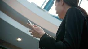 Gelukkige jonge vrouw die slimme telefoon in winkelcomplex met behulp van Onderneemster freelancer met smartphone in luchthavente stock footage