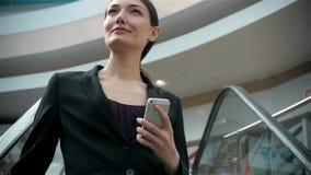 Gelukkige jonge vrouw die slimme telefoon in winkelcomplex met behulp van Onderneemster freelancer met smartphone in luchthavente stock videobeelden