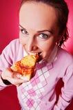 Gelukkige jonge vrouw die stuk van pizza eet Stock Afbeeldingen