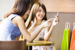 Gelukkige jonge vrouw die telefoon in koffiewinkel bekijken Stock Fotografie