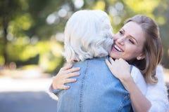 Gelukkige jonge vrouw die teruggetrokken moeder in het park koesteren royalty-vrije stock fotografie