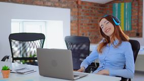 Gelukkige jonge vrouw die terwijl het luisteren aan luide muziek in hoofdtelefoons die bij bureau met laptop zitten zingen stock videobeelden