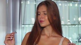 Gelukkige jonge vrouw die tussen twee diamantringen kiezen voor verkoop stock videobeelden