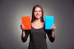 Gelukkige jonge vrouw die twee boeken tonen Royalty-vrije Stock Foto's