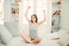 Gelukkige jonge vrouw die van zonnige ochtend op het bed genieten stock fotografie