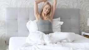 Gelukkige jonge vrouw die van zonnige ochtend op het bed genieten stock videobeelden