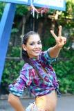 Gelukkige jonge vrouw die vredesteken in openlucht in de zomer tonen Royalty-vrije Stock Foto