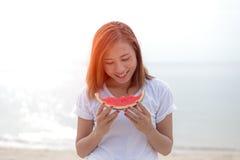 Gelukkige jonge vrouw die watermeloen op het strand eten de jeugdlevensstijl Geluk, vreugde, vakantie, strand, stock afbeeldingen