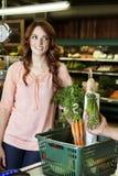 Gelukkige jonge vrouw die weg terwijl de groente van de handholding in supermarkt kijken Royalty-vrije Stock Foto