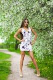 Gelukkige jonge vrouw die in witte kleding in de lentepark lopen stock afbeelding