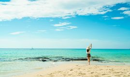 Gelukkige jonge vrouw die in witte overhemden en borrels bij zandstrand lopen Het ontspannen van en het genieten van van vakantie royalty-vrije stock foto's
