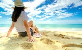Gelukkige jonge vrouw die in witte overhemden en borrels bij zandstrand zitten Het ontspannen van en het genieten van van vakanti stock afbeelding