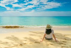 Gelukkige jonge vrouw die in witte overhemden en borrels bij zandstrand zitten Het ontspannen van en het genieten van van vakanti royalty-vrije stock foto